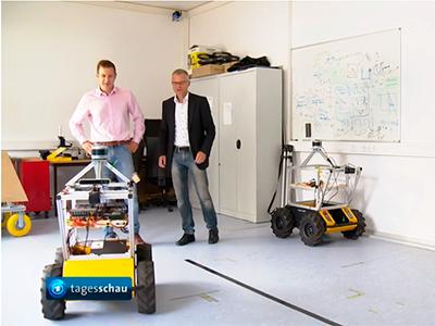 Prof. Dr. Cyrill Stachniss und Prof. Dr. Kuhlmann mit einem der Forschungsroboter