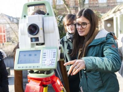 Schülerinnen bei einem Schnupper-Uni-Workshop der Geodäsie und Geoinformation mit einem elektronischen Tachymeter zur 3D-Koordinatenbestimmung. (© Barbara Frommann / Uni Bonn)