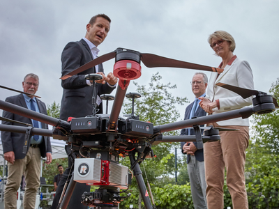 """Cyrill Stachniss, one of the two spokespersons of the """"PhenoRob"""" Cluster of Excellence, explains to Anja Karliczek how the use of robots and drones is being researched for the agricultural economy of the future. (© Photo: Volker Lannert / Uni Bonn)"""